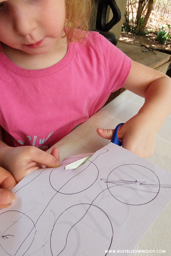 toddler cutting circles for Christmas card