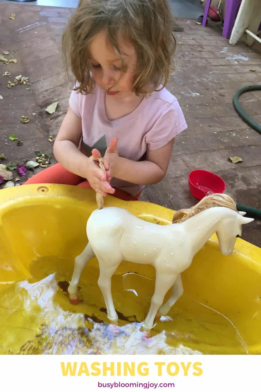 Preschooler washing her toys as an outdoor activity