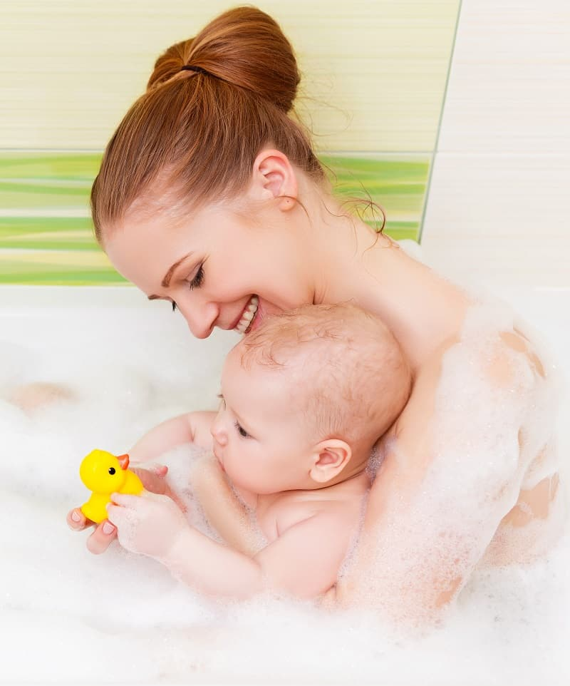 You might need to jump in the bath with baby when learning how to bathe your newborn