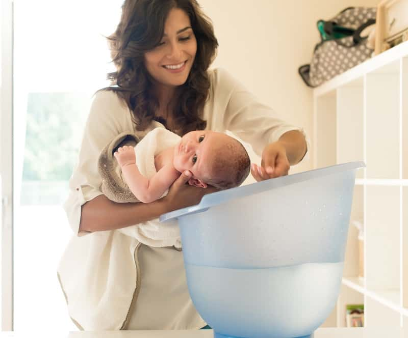 To wash a newborns hair, lie them along your forearm and sprinkle water over the head into a bucket or bath