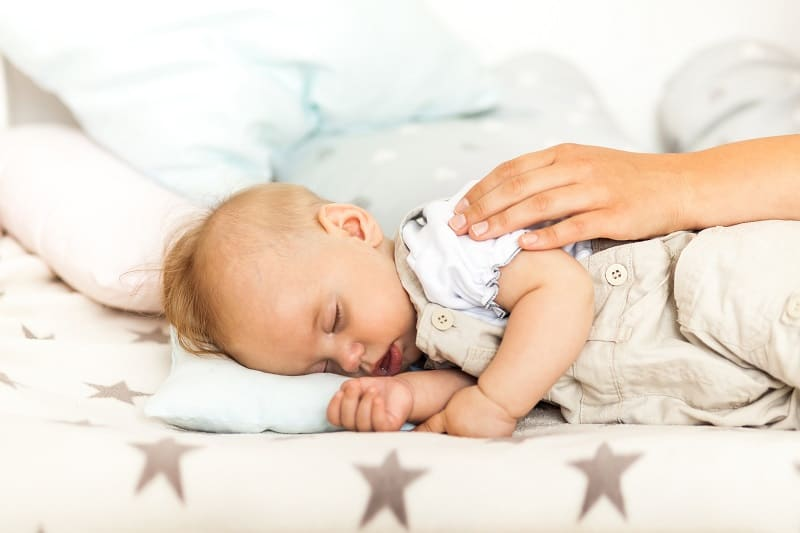 Side-lying and patting (plus a swaddle and minus the pillow) can help settle baby fully to sleep in the bassinet, avoiding the need to transfer